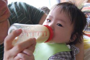 パパにミルクをもらっている赤ちゃん