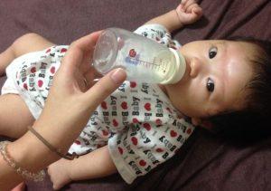 布団でごろんしてミルクを飲む赤ちゃん