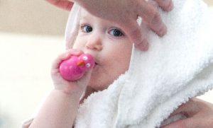 おもちゃを口でくわえる赤ちゃん
